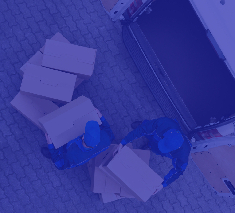 Blue image with overhead view of two men moving boxes