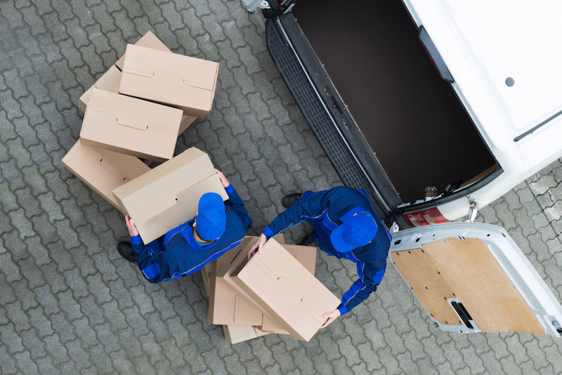 Overhead view of two men moving boxes